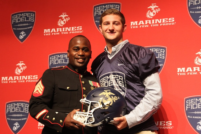 Sgt. Allen Leonard Jr., canvassing recruiter, Marine Corps Recruiting Station Columbia and Austin Kendall, quarterback, Cuthbertson High School pose for a photo after the Semper Fidelis All-American Bowl jersey presentation at Cuthbertson High School on Nov.3, 2015. Kendall was presented with his jersey in front of his football team, coaching staff, friends and family.
