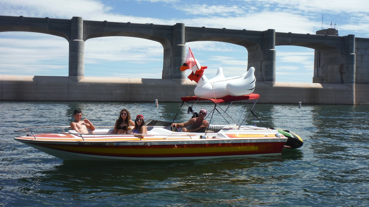 CONCHAS LAKE, N.M. – Lake visitors in their boat with their mascot Sasha the swan, Sept. 6, 2015. Sasha has her ski flag and life jacket on.  Sasha has been visiting the lake all summer. Photo by Valerie Mavis.