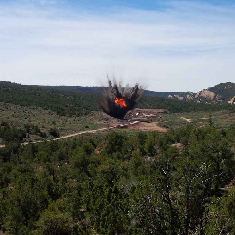 FORT WINGATE, N.M. – The controlled detonation of an M66A1, 2000-pound explosive bomb of the World War II-era. The bomb was excavated by a Corps of Engineers contractor at a depth of over 30 feet below grade.   It is suspected that the bomb was a part of a previous ammunition disposal operation conducted at the site in the past that was not properly prepared. The explosion failed to destroy the bomb, and it was covered by dirt from the original blast. After the bomb was unearthed this time, it was temporarily stored in a magazine until weather, environmental concerns, explosives safety and operational issues with equipment at the job site could be resolved. On May 20, 2015, the bomb was removed from storage and carefully placed in a prepared pit on a hillside and covered with 10 feet of dry soil. The photo captures the moment the fireball from the explosion breached the soil cover.  Photo by Henry Domme. This was a 2015 photo drive entry.