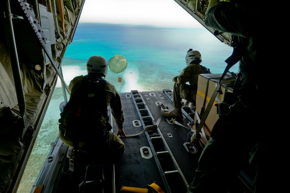 Cpl. Teome Matamua and Sgt. Phillip McIllvaney, Australian Army 176th Air Dispatch Squadron loadmasters, deliver the first low-cost, low-altitude bundle of Operation Christmas Drop 2015 to the island of MogMog, Dec. 8, 2015. Australian and Japanese C-130 aircrews for the first time joined U.S. Airmen during the 64th year of Operation Christmas Drop – a Humanitarian Aid/Disaster Relief training event where C-130 aircrews perform LCLA airdrops on unsurveyed drop zones while providing critical supplies to 56 islands throughout the Commonwealth of the Northern Marianas, Federated States of Micronesia and Republic of Palau. It highlights the U.S. and allied airpower capabilities to orient and respond to activities in peacetime and crisis. (U.S. Air Force photo/Staff Sgt. Katrina Brisbin)