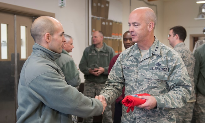 Capt. Wesley Sheppard, 366th Aircraft Maintenance Unit officer in charge, presents Maj. Gen. Glenn Davis, Air Force Life Cycle Management Center mobilization assistant to the commander, with the AMU coin and squadron t-shirt at Mountain Home Air Force Base, Idaho, Dec. 3, 2015. Davis came to see first-hand the capabilities of Mountain Home's Strike Eagles. (U.S. Air Force photo by Senior Airman Malissa Lott/RELEASED)
