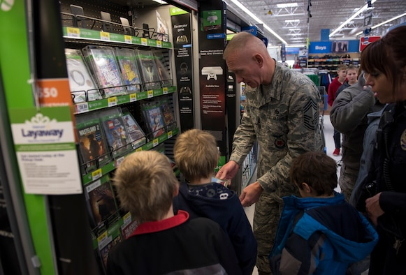 Chief Master Sgt. Richard Lien Jr., 366th Civil Engineer Squadron fire department chief, looks over different gaming options with a few of the participants of Shop with a Cop, Dec. 5, 2015, in Mountain Home, Idaho. Many of the children purchased gifts for their families during the event. (U.S. Air Force photo by Airman 1st Class Connor J. Marth/Released)