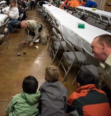 Local law enforcement race cars back and forth during the Shop with a Cop event, Dec. 5, 2015, at the Mountain Home, Idaho Elk Lodge. Officers encouraged the children by being the first to join in the festivities. (U.S. Air Force photo by Airman 1st Class Connor J. Marth/Released)