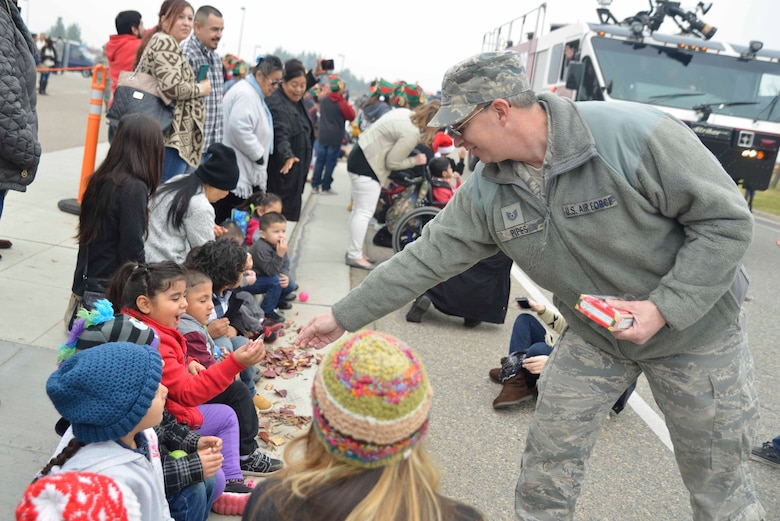 U.S. Air Force Tech. Sgt. Gordon Pipes, 144th Communications Flight information technology specialist, passes candy out to children during the 29th Annual Silent Sleigh at the Fresno Air National Guard Base Dec. 9, 2015. Silent Sleigh, similar to a Christmas carnival, is an event geared towards deaf and hard of hearing children from the Fresno, Clovis, Madera and surrounding county areas. (U.S. Air National Guard photo by Senior Airman Klynne Pearl Serrano)
