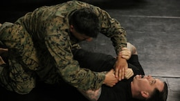 A student in the Martial Arts Instructor Course grapples with Staff Sgt. Roger Nelson, the chief instructor of the course, during a training session at Marine Corps Base Camp Lejeune, N.C., Dec. 4, 2015. The three-week long course will qualify its students to be Martial Arts instructors. The course's development of endurance, strength, fighting ability and knowledge will benefit Marines for future operations in any location. (U.S. Marine Corps photo by Cpl. Paul S. Martinez/Released)