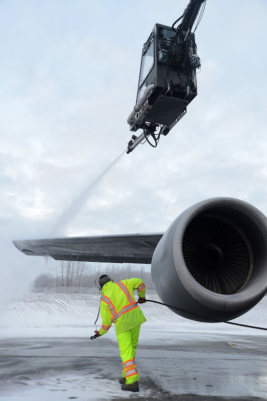Staff Sgts. Tyler Derr, top, and Justin Fleming, from the 732nd Air Mobility Squadron, deice an aircraft's wing on the flightline at Joint Base Elmendorf-Richardson, Alaska, Dec. 3, 2015. There is always a person in the truck, one in the deicer and one on the ground to make sure the aircraft is deiced all around. (U.S. Air Force photo/Airman 1st Class Christopher R. Morales)