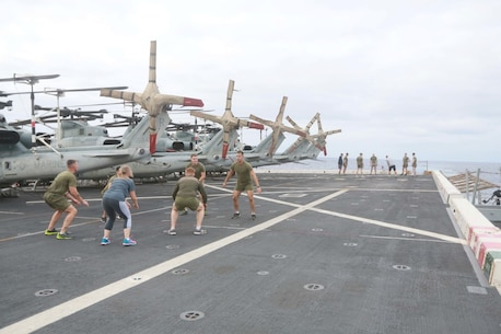PACIFIC OCEAN (Dec. 7, 2015) U.S. Marines with 1st Light Armored Reconnaissance Detachment, Battalion Landing Team 3rd Battalion, 1st Marine Regiment, 15th Marine Expeditionary Unit, work out with family members on the flight deck aboard the USS Anchorage (LPD 23). The 15th MEU is coming to the end of deployment and hosting a Tiger Cruise for family members to showcase life aboard the Anchorage. (U.S. Marine Corps photo by Sgt. Steve H. Lopez/Released)