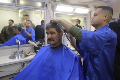 PACIFIC OCEAN (Dec. 7, 2015) U.S. Marines with 15th Marine Expeditionary Unit and family members receive haircuts in the barbershop aboard the USS Anchorage (LPD 23). The 15th MEU is coming to the end of deployment and hosting a Tiger Cruise for family members to showcase life aboard the Anchorage. (U.S. Marine Corps photo by Sgt. Steve H. Lopez/Released)