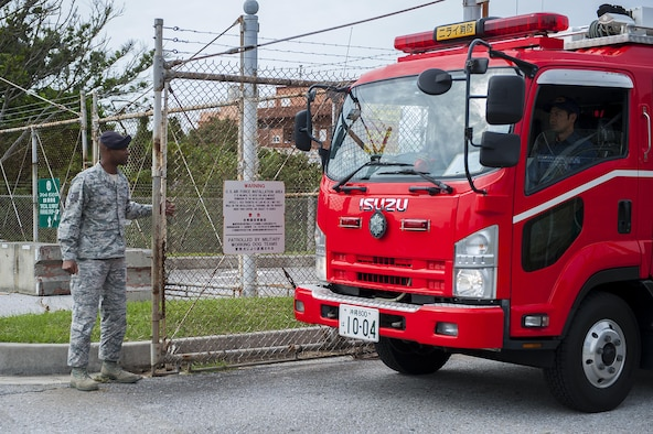 U.S. Air Force Tech Sgt. Teddy Poole, 18th Security Forces Squadron police service NCO in charge, opens a gate for a Nirai Fire Department vehicle during an exercise Dec. 3, 2015, at Kadena Air Base Japan. Base entry was provided for first responders who may need to use base roads in the instance of a flooding that blocks off other routes. (U. S. Air Force photo by Airman 1st Class Corey M. Pettis/Released)