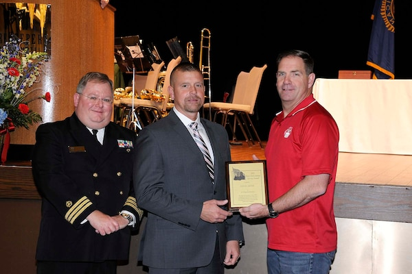 "Steve Carter (center) receives the Hart-Dole-Inouye Federal Center Service Award from DLA Disposition Services Director Mike Cannon (right) and Retired Navy Cmdr. T.R. Shaw for demonstrating the ""spirit of service"" synonymous with the center and its namesakes."