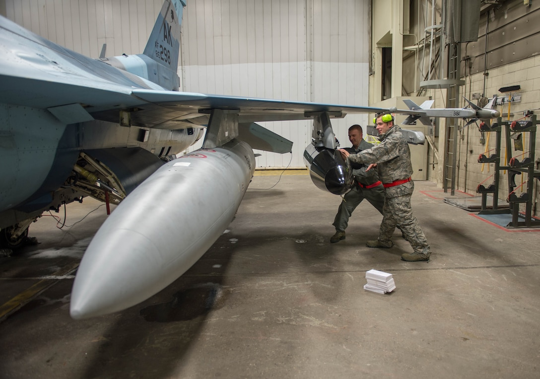 Staff Sgt. Robert Knickle (left) and Timothy Smith, from the 354th Aircraft Maintenance Squadron, push luggage into a pod on an F-16 Fighting Falcon fighter aircraft Dec. 7, 2015, at Eielson Air Force Base, Alaska. More than 30 maintenance Airmen worked an early shift to help launch several jets to Tyndall Air Force Base, Florida, for CHECKERED FLAG 16-1, a large-force exercise that simulates a large number of aircraft in a deployed environment to cross-check weapons systems. (U.S. Air Force photo by Staff Sgt. Shawn Nickel/Released)