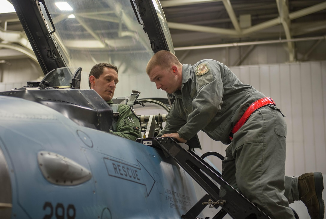 Staff Sgt. Robert Knickle a 354th Aircraft Maintenance Squadron crew chief, assists Lt. Col. Mark Sletten, the F-35 Program Integration Officer, into an F-16 Fighting Falcon fighter aircraft Dec. 7, 2015, at Eielson Air Force Base, Alaska. More than 30 maintenance Airmen worked an early shift to help launch several jets to Tyndall Air Force Base, Florida, for CHECKERED FLAG 16-1, a large-force exercise that simulates a large number of aircraft in a deployed environment to cross-check weapons systems. (U.S. Air Force photo by Staff Sgt. Shawn Nickel/Released)