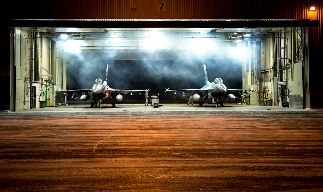 Exhaust billows as two F-16 Fighting Falcon fighter aircraft engines start in Dock 7 at Eielson Air Force Base, Alaska, Dec. 7, 2015. More than 30 maintenance Airmen worked an early shift to help launch several jets to Tyndall Air Force Base, Florida, for CHECKERED FLAG 16-1, a large-force exercise that simulates a large number of aircraft in a deployed environment to cross-check weapons systems. (U.S. Air Force photo by Staff Sgt. Shawn Nickel/Released)