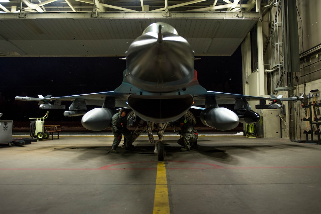 Staff Sgt. Robert Knickle (left) and Timothy Smith, from the 354th Aircraft Maintenance Squadron, perform the last pre-flight checks on an F-16 Fighting Falcon fighter aircraft Dec. 7, 2015, at Eielson Air Force Base, Alaska. More than 30 maintenance Airmen worked an early shift to help launch several jets to Tyndall Air Force Base, Florida, for CHECKERED FLAG 16-1, a large-force exercise that simulates a large number of aircraft in a deployed environment to cross-check weapons systems. (U.S. Air Force photo by Staff Sgt. Shawn Nickel/Released)