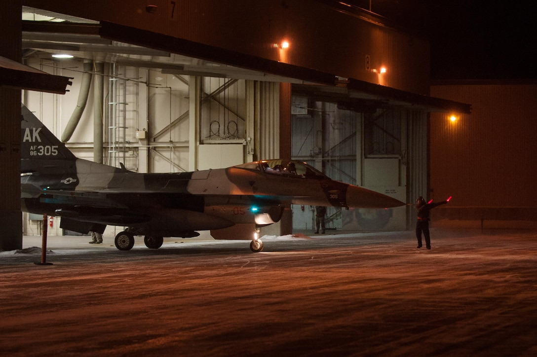 A crew chief with the 354th Aircraft Maintenance Squadron, ushers an F-16 Fighting Falcon fighter aircraft out of the bay onto the taxiway Dec. 7, 2015, at Eielson Air Force Base, Alaska. More than 30 maintenance Airmen worked an early shift to help launch several jets to Tyndall Air Force Base, Florida, for CHECKERED FLAG 16-1, a large-force exercise that simulates a large number of aircraft in a deployed environment to cross-check weapons systems. (U.S. Air Force photo by Master Sgt. Joseph Swafford/Released)