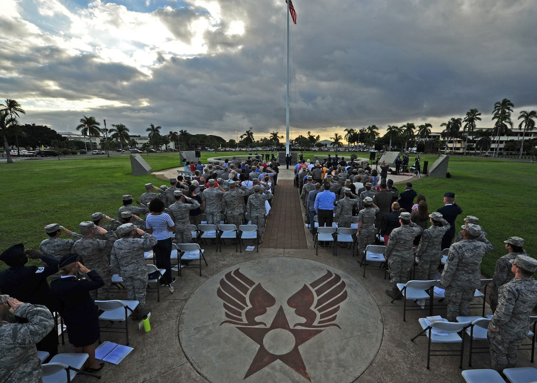 Military members salute during the singing of the national anthem at the Hickam Field Remembrance Ceremony hosted by the 15th Wing on Joint Base Pearl Harbor-Hickam, Hawaii, Dec. 7, 2015. Survivors and their family members attended the 74th remembrance ceremony, which honored the men and women who lost their lives on Hickam Field during the two waves of attacks launched by the Imperial Japanese Navy on Dec. 7, 1941. (U.S. Air Force photo/Tech. Sgt. Aaron Oelrich)