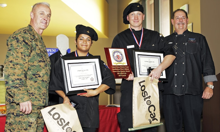 Cpl. Monica Rios and Lance Cpl. Marshall Griffiths, Food Service Specialists, Food service Company, Headquarters Regiment, 1st Marine Logistics Group, pose for a photograph with Col. Jeff Arruda, left, Chief-of-Staff, Marine Corps Base Camp Pendleton, Marine Corps Installations-West and Donovan Brown, right, head chef with Sodexo, after taking first place honors at the MCI-West Chef of the Quarter culinary competition here, Dec. 3.