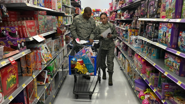 Senior Master Sgt. Martez Banks, 419th Aircraft Maintenance Squadron first sergeant, and Master Sgt. Ruby Contreras, 419th Civil Engineer Squadron first sergeant, search a toy aisle at a Walmart in Salt Lake City for Christmas wish-list items. A group of reservists from the 419th Fighter Wing volunteered to shop for families in need this holiday season. (U.S. Air Force photo/Bryan Magaña)