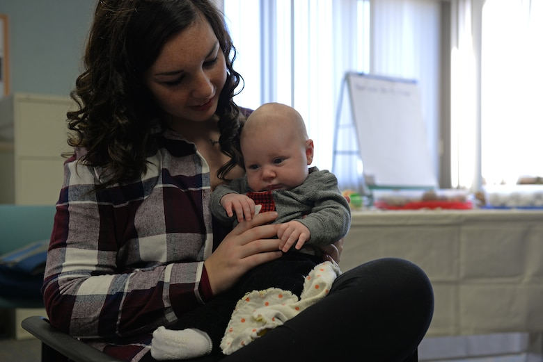 Airman 1st Class Kelsey Palmer, a new mom with the 375th Force Support Squadron, holds her 6-week old son during a Centering Pregnancy support group reunion, Dec. 1, 2015, Belleville, Illinois. The support group's goal is to help moms-to-be prepare for motherhood and find other military families going through the same family changes. (U.S. Air Force photo by Airman 1st Class Erica Holbert-Siebert)