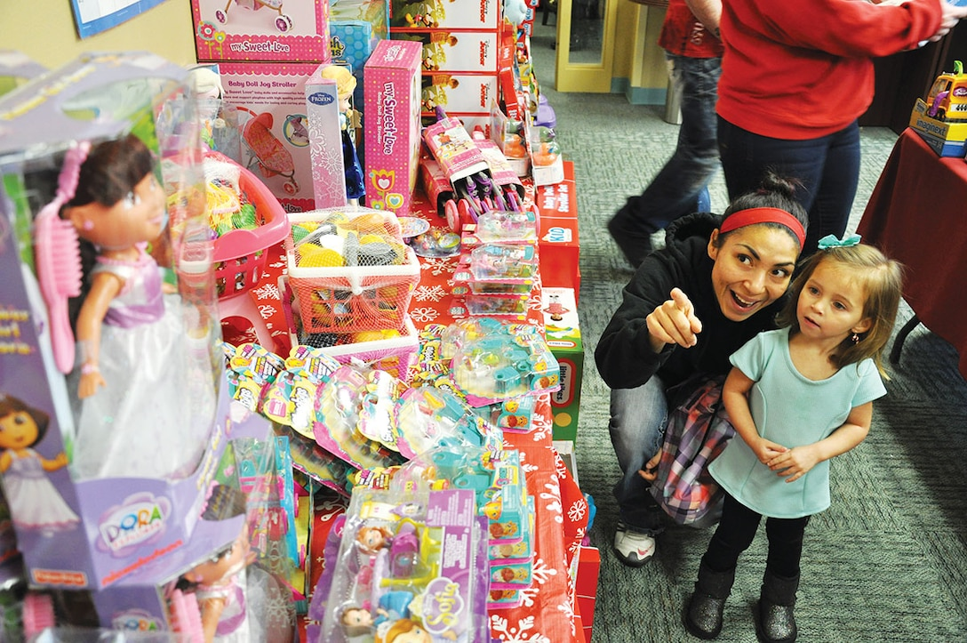 Gloria Schiers, wife of Staff Sgt. Nathan Schiers, 962d Airborne Air Control Squadron communications systems operator, points out a doll to her daughter Kambryn, 3, at the third annual Operation Homefront holiday toy distribution event at Joint Base Elmendorf-Richardson Dec. 4. (U.S. Air Force photo/Staff Sgt. Wes Wright)