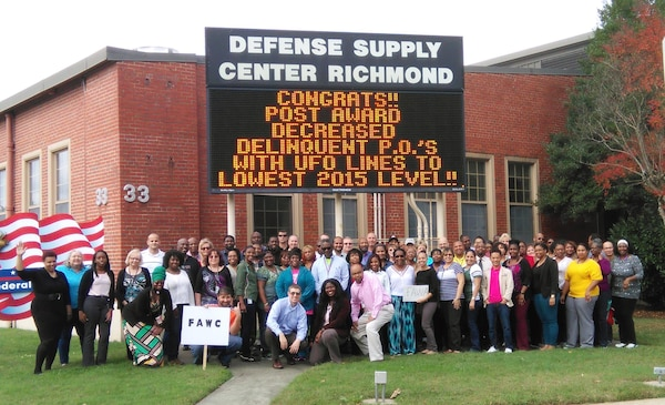 Defense Logistics Agency Aviation Supplier Operations Directorates' Contract Administration team members proudly pose under the flashing marquee at Defense Supply Center Richmond, Virginia. Nov. 11, 2015.