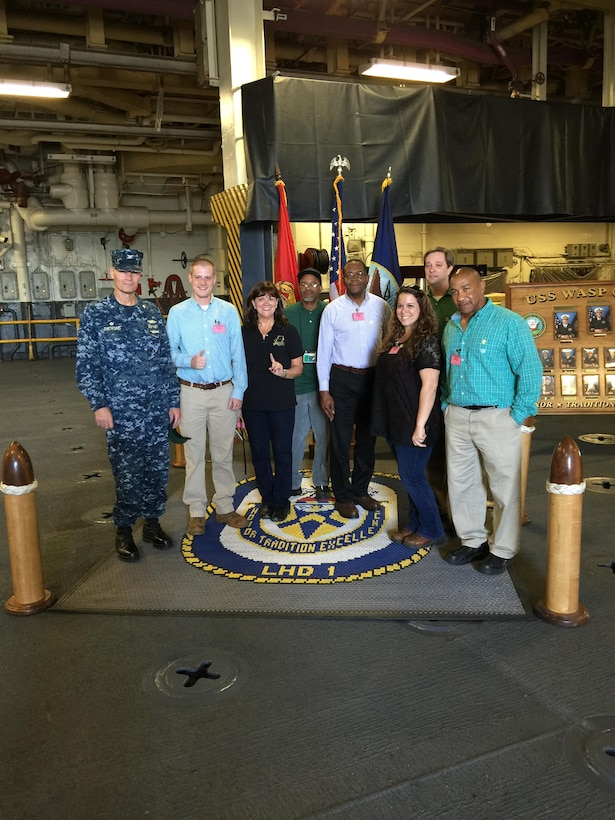 DLA Distribution Norfolk, Va., and OSHA staff stand on the quarterdeck of the USS Wasp (LHD 1) during their recent STAR recertification visit.