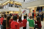 Children from the McNamara Headquarters Complex Child Development Center's kindergarten class look on as Santa and his elves make their way down the stairs at the HQC Tree Lighting and Holiday Social Dec. 9.