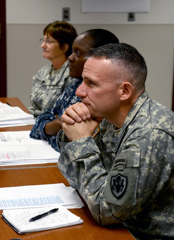Col. Martin Downie, the commandant of the Defense Information School at Fort Meade, Md., listens to an instructor Nov. 9 during an Instructor Training Course class at the school. The Instructor Training Course trains prospective faculty members on effective teaching methods.
