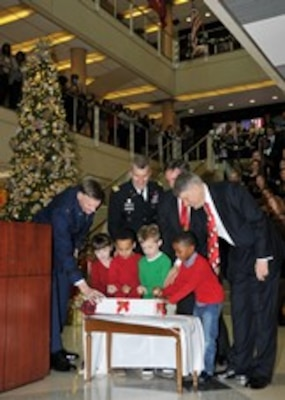 McNamara Headquarters Complex senior leaders assist children from the HQC Child Development Center's kindergarten class as they pull the lever that illuminates the tree at the HQC Tree Lighting and Holiday Social Dec. 9.