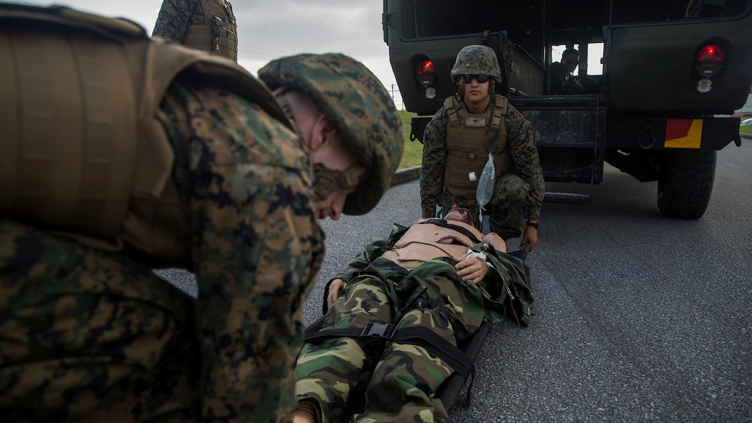 Hospital corpsmen lift a simulated casualty into M997 ambulance during a casualty evacuation drill at Marine Corps Air Station Futenma, Okinawa, Japan Dec. 8, 2015. The casevac course is two weeks long and gives the students a better understanding of what it means to be a corpsman. The corpsmen are with various units with III Marine Expeditionary Force.