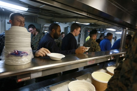 PACIFIC OCEAN (Dec. 9, 2015) U.S. Marines and Sailors with the 15th Marine Expeditionary Unit, USS Anchorage (LPD 23), and family members stand in line for ice cream during an ice cream social aboard the Anchorage. The 15th MEU is coming to the end of deployment and hosting a Tiger Cruise for family members to showcase life aboard the Anchorage. (U.S. Marine Corps photo by Sgt. Steve H. Lopez/Released)