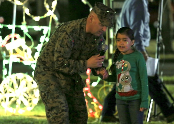 Col. Peter Buck gets assistance from a child in the crowd to countdown the 27th Annual Tree Lighting Ceremony aboard Laurel Bay Dec. 3. Buck instructs the crowd of service members and their families to help countdown the official lighting. Buck is the commanding officer of Marine Corps Air Station Beaufort.