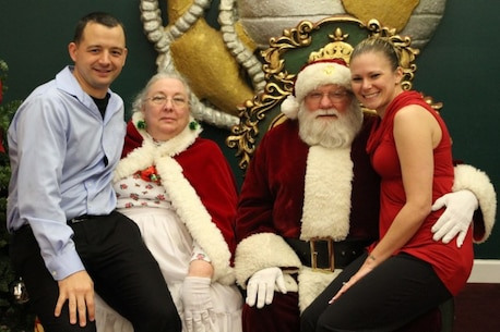 Staff Sgt. Richard Weiss and his wife, Staff Sgt. Kimberly Weiss pose with Santa Claus during a Christmas Party Dec. 8, 2015 at Traditions on Parris Island, S.C. 6th Marine Corps District holds an annual Christmas party to celebrate the holidays with the Marines and their families to boost morale and camaraderie among one another.(Official Marine Corps photo by Cpl. Diamond N. Peden/Released)