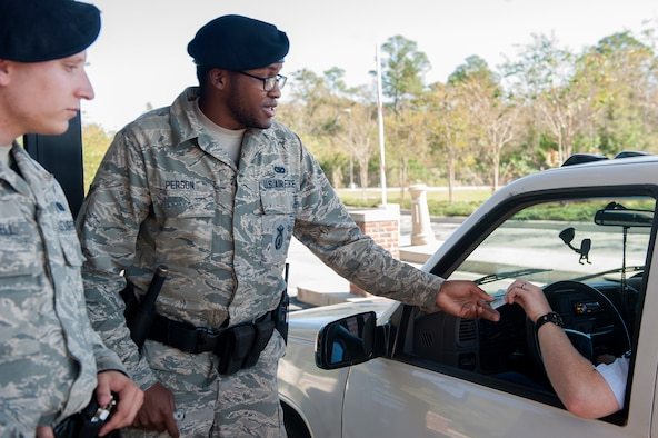 U.S. Air Force Airman 1st Class Nikolas Truesdell, left, and Airman Paul Person, 23d Security Forces Squadron installation entry controllers, check identification, Nov. 11, 2015, at Moody Air Force Base, Ga. The IECs also conduct Random Anti-Terrorist Measures, during which they may ask to see someone's driver's license and vehicle registration. (U.S. Air Force photo by Airman 1st Class Kathleen D. Bryant/Released)