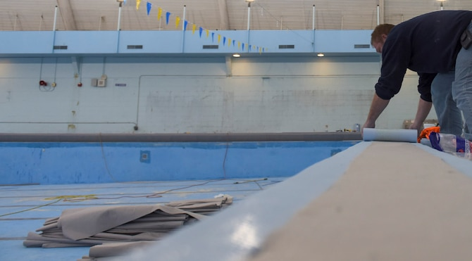Chuck Mason, project manager for RenoSys construction company out of Indianapolis, Indiana, lays the top portion of the pool liner, Dec. 8, 2015 at Mountain Home Air Force Base, Idaho. The pool will be closed until April for the replacement of the pool liner and the installment of a slick-resistant floor on the pool deck. (U.S. Air Force photo by Senior Airman Jeremy L. Mosier/Released)