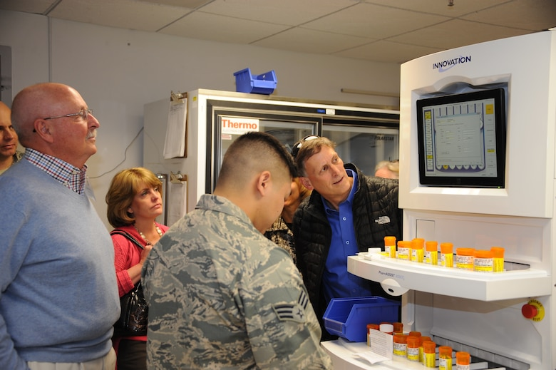 U.S. Air Force Senior Airman Paul Ebiya, 355th Medical Support Squadron pharmacy technician, shows members of the base's Honorary Commanders Program a demonstration  of the new pharmacy machine, the Pharmassist, at Davis-Monthan Air Force Base, Ariz., Dec. 2, 2015. The Pharmassist can refill 100 prescriptions per hour with little to no mistakes. (U.S. Air Force photo by Airman 1st Class Ashley N. Steffen/Released)