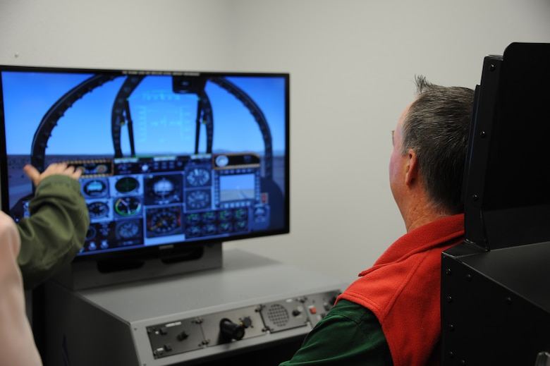 U.S. Air Force Capt. Kimberly Dowd, 355th Aerospace Medical Squadron human performance flight commander, shows Chris Edwards, 355th Operations Group honorary commander and owner of Tucson Appliance, how a static flight simulator operates at Davis-Monthan Air Force Base, Ariz., Dec. 2, 2015. With an attachment above  the simulator allows pilots to experience reduced oxygen induces hypoxia without the dangers of flying. (U.S. Air Force photo by Airman 1st Class Ashley N. Steffen/Released)