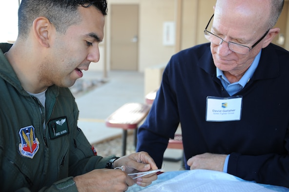 U.S. Air Force Capt. Miguel Valencia, 563rd Operational Support Squadron flight surgeon, shows David Gallaher, 924th Fighter Group honorary commander and managing member and designated broker for Tucson Industrial Realty LLC, how to thread a suture needle at Davis-Monthan Air Force Base, Ariz., Dec. 2, 2015.  D-M AFB's honorary commanders toured the 355th Medical Group with stops that included the Medical Clinic and the Health and Wellness Center. (U.S. Air Force photo by Airman 1st Class Ashley N. Steffen/Released)