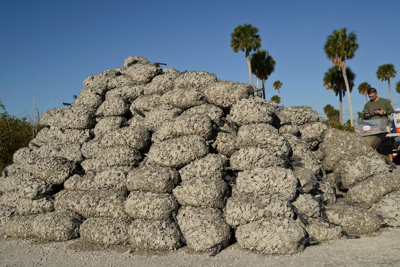 Eight hundred bags of shells sit in a pile at the Marina on MacDill Air Force Base, Fla., Dec. 11, 2015. Volunteers gathered, bagged, transported and installed 14 tons of shells to build an oyster reef habitat along the shoreline. (U.S. Air Force photo by Senior Airman Vernon L. Fowler Jr./Released)