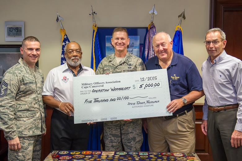 Brig. Gen. Wayne Monteith, 45th Space Wing commander, (center), and Chief Master Sgt. Jason Lamoureux, 45th command chief, (left), accept a $5,000 check on behalf of members of Military Officers Association of America, Cape Canaveral Chapter, in support of Operation Warmheart, Dec. 4, 2015, at Patrick Air Force Base, Fla. Every year around the holidays, MOAA donates money to Operation Warmheart to help military members from all of the different branches assigned to Patrick Air Force Base and Cape Canaveral Air Force Station. The Patrick AFB First Sergeant's Council is responsible for Operation Warmheart and operates solely from donations and money is used to assist Airmen and their families within the wing and its tenant units. (U.S. Air Force photo/Benjamin Thacker) (Released)