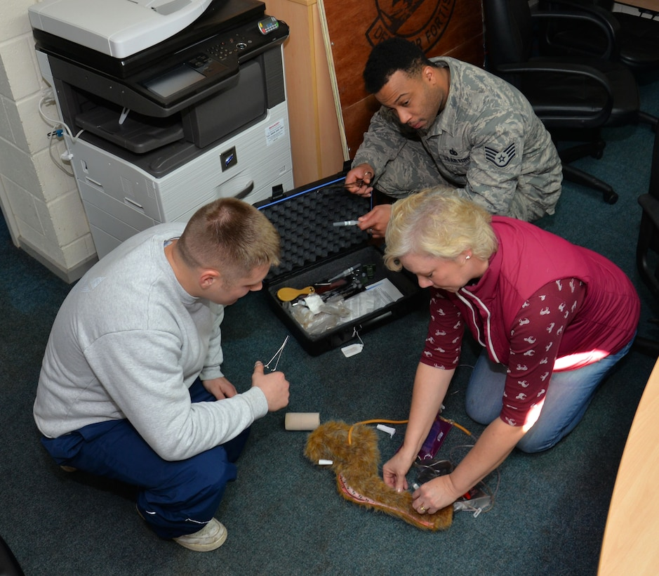 Deborah Black, right, 100th Security Forces Squadron kennel attendant; U.S. Air Force Staff Sgt. Michael Junkins, center, 100th SFS Military Working Dog handler; and U.S. Air Force Staff Sgt. Roy Carter, 100th SFS MWD trainer, check a medical kit for the 100th SFS MWDs Dec. 4, 2015, on RAF Mildenhall, England. The personnel check the dogs throughout the day and night to make sure they are fit, healthy and ready for duty. In the field when there isn't a veterinarian, the handlers are trained to administer first aid to their dog. (U.S. Air Force photo by Gina Randall/Released)