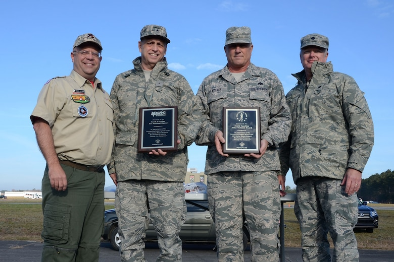 Doug Stone, the Indian Waters Council executive, presents U.S. Air Force Brig. Gen. Russell Rushe, Assistant Adjutant General for Air, with plaques of appreciation for the Air and Army National Guard at McEntire Joint National Guard Base, S.C., during the Swamp Fox Camporee Dec. 6, 2015. The event was hosted by the South Carolina National Guard to allow Cub Scouts and Boy Scouts the opportunity to interact with Guardsmen and compete to earn various merit badges. (U.S. Air National Guard photo by Airman Megan Floyd/RELEASED))