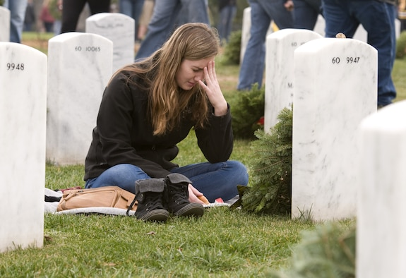 Emily Johnson sheds tears in front of the headstone for her older brother, Army 1st Lt. David Andrew Johnson, who was killed by an improvised explosive device in 2012. Johnson and other family members of fallen troops and thousands of volunteers were at the Arlington National Cemetery on Dec. 12, 2015, for Wreaths Across America Day, an event to honor those who died defending the country. (U.S. Air Force photo/Sean Kimmons)