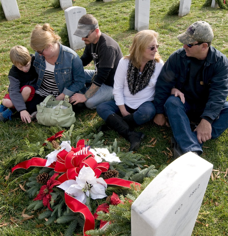 Family members of Army Sgt. 1st Class Johnathan McCain, who was killed in Afghanistan in 2011, spend time at his headstone at Arlington National Cemetery on Dec. 12, 2015, for Wreaths Across America Day, an event to honor those who died defending the country. (U.S. Air Force photo/Sean Kimmons)