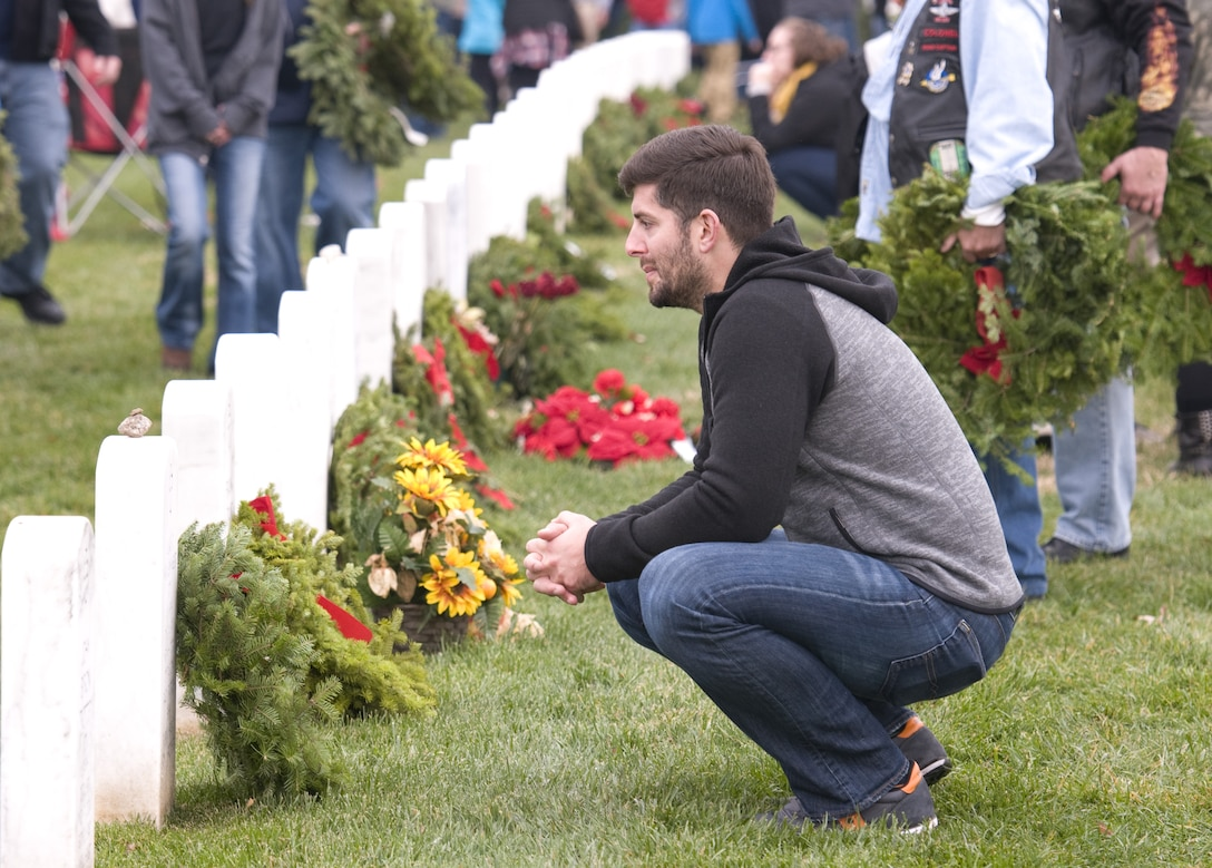 A volunteer looks at the headstone of a fallen service member at Arlington National Cemetery on Dec. 12, 2015, during Wreaths Across America Day, an event to honor those who died defending the country. (U.S. Air Force photo/Sean Kimmons)