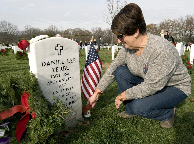 Susan Zebre prepares to place a wreath on the headstone for her son, Tech. Sgt. Daniel Lee Zerbe, who was one of 30 U.S. troops killed when a CH-47 Chinook helicopter was shot down in Afghanistan in 2011. Susan and other family members of fallen troops and thousands of volunteers were at the Arlington National Cemetery on Dec. 12, 2015, for Wreaths Across America Day, an event to honor those who died defending the country. (U.S. Air Force photo/Sean Kimmons)