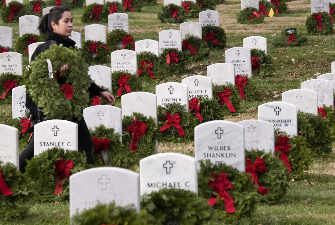 A volunteer carries a wreath to a headstone in Arlington National Cemetery on Dec. 12, 2015, for Wreaths Across America Day, an event to honor those who died defending the country. (U.S. Air Force photo/Sean Kimmons)