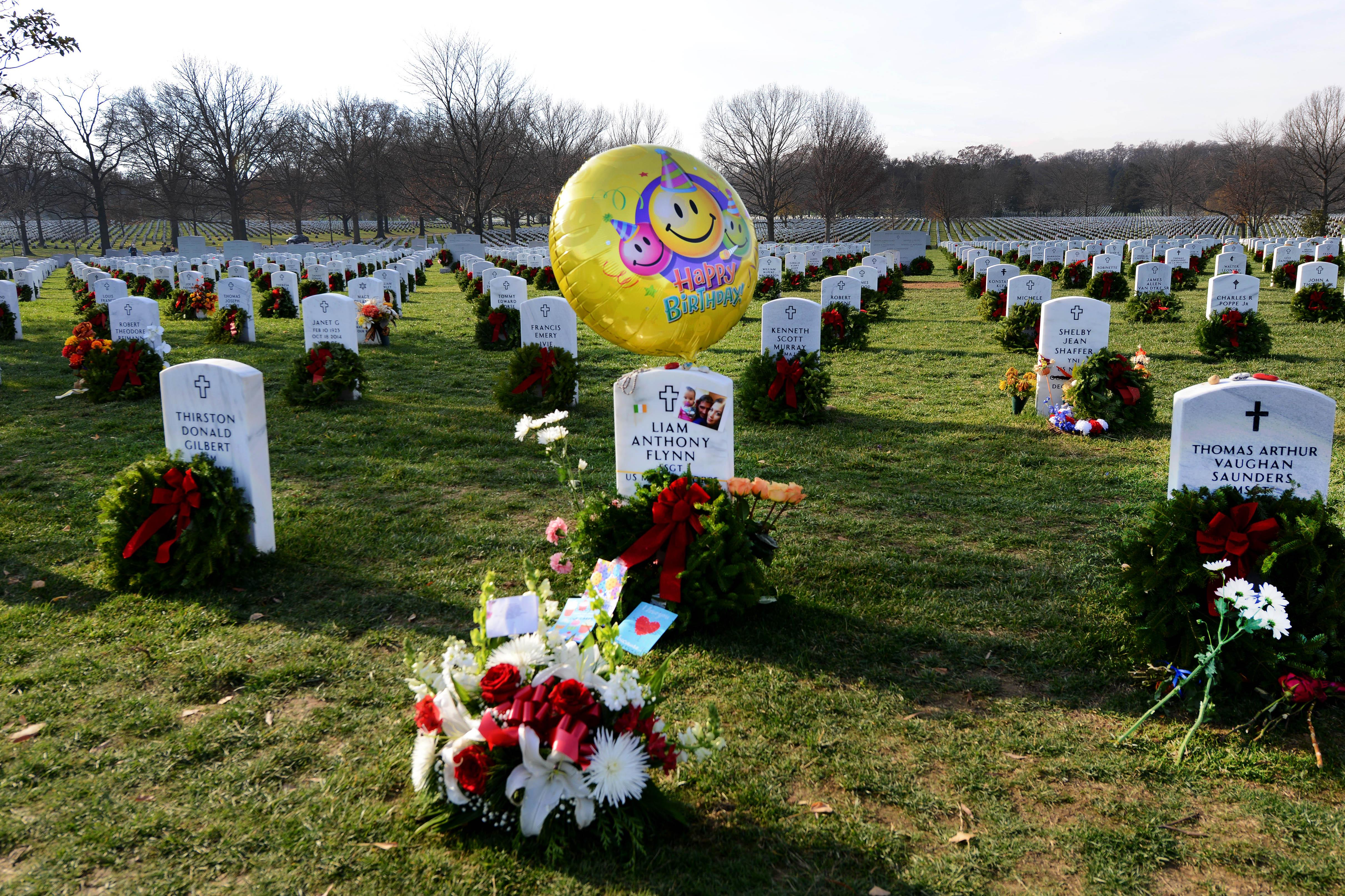 Us department of defense photos photo gallery a wreath decorated with flowers and birthday ornaments is placed at a grave marker izmirmasajfo