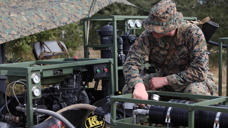 Lance Cpl. Quentin J. Stallings evaluates the settings on a water filter and pump at Marine Corps Auxiliary Landing Field Bogue, N.C., Dec. 9, 2015. Marines with Marine Wing Support Squadron 271's Engineer Company participated in a cantonment and capabilities field exercise to practice and improve their knowledge of their jobs while in a deployed environment. The weeklong exercise featured events such as airfield damage repair, water purification, medium and heavy lifting missions, with the construction of an expedient road for a vertical take-off and landing aircraft pad. Stallings is a water support technician with MWSS-271.