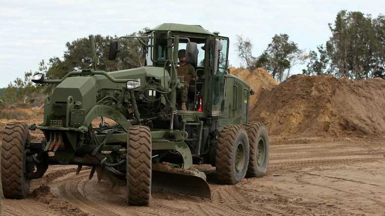 A Marine operates a motor grader to level the ground for a vertical take-off and landing aircraft pad at Marine Corps Auxiliary Landing Field Bogue, N.C., Dec. 9, 2015. Marines with Marine Wing Support Squadron 271's Engineer Company participated in a cantonment and capabilities field exercise to practice and improve their knowledge of their jobs while in a deployed environment. The weeklong exercise featured events such as airfield damage repair, water purification, medium and heavy lifting missions, with the construction of an expedient road for a vertical take-off and landing aircraft pad.